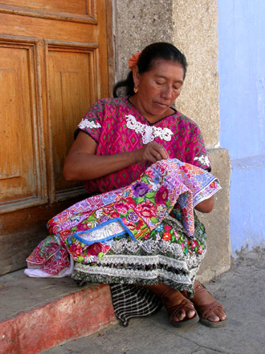 A mayan woman sitting on a doorstep embroidering