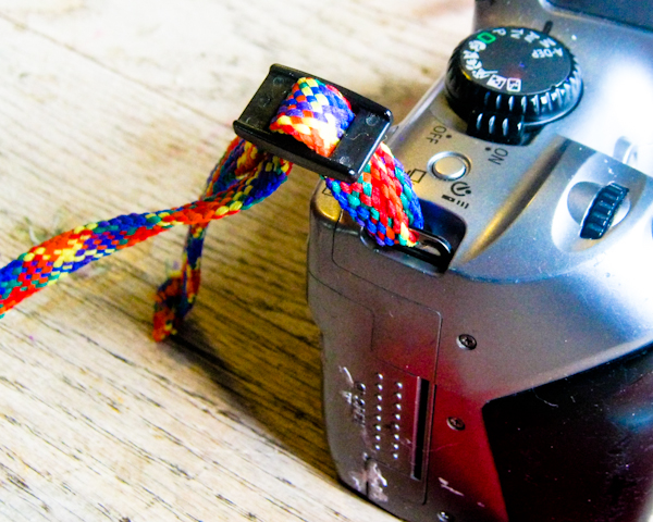 Fit the plastic slides onto the narrow webbing before you put the strap on the camera