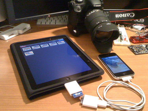An iPad, iPhone, and Canon camera on the desk