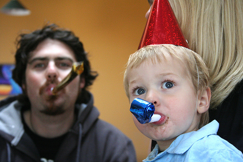 A kid using a party blower