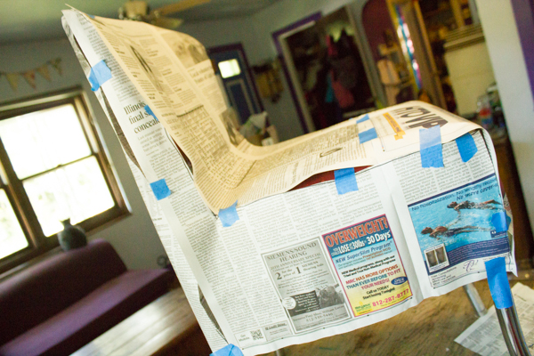 Use plenty of newspaper and plenty of tape to make your chair cover pattern.