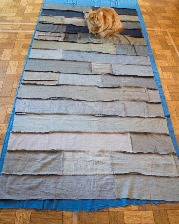cat sitting on denim strip quilt