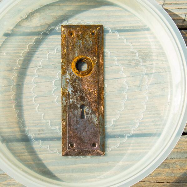 rusted antique door plate soaking in vinegar
