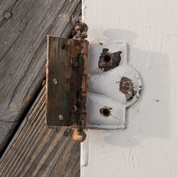 antique door hinge painted with several layers of paint